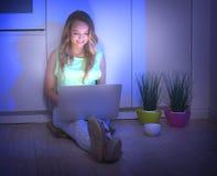 Muchacha de la belleza que se sienta en un piso en la noche y que usa el ordenador portátil Imagen de archivo libre de regalías