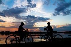 Muchacha de la bici de la silueta en la puesta del sol Imagenes de archivo