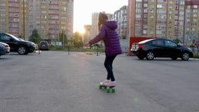 Muchacha de la cámara lenta que anda en monopatín en la calle de la ciudad mientras que iguala puesta del sol Monopatín del monta metrajes