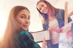 Muchacha de la castaña que mira en cámara mientras que toma el certificado Imagen de archivo