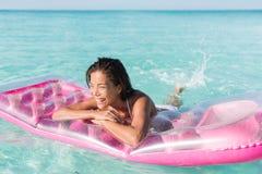 Muchacha de la diversión de la playa que salpica el agua en el océano Foto de archivo libre de regalías