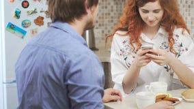 Muchacha de la ensenada con el pelo rojo rizado con un teléfono, un café de consumición del hombre almacen de video