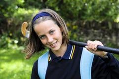 Muchacha de la escuela con el palillo de hockey Fotos de archivo