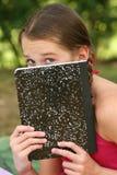 Muchacha de la escuela con un cuaderno al aire libre Fotos de archivo