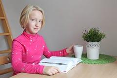 muchacha de la Escuela-edad que lee un libro mientras que se sienta en una tabla en un apartamento Fotografía de archivo libre de regalías