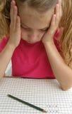 Muchacha de la escuela en problemas con matemáticas Imagenes de archivo