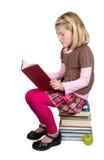 Muchacha de la escuela que lee un libro Foto de archivo libre de regalías