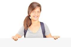 Muchacha de la escuela que presenta detrás del panel blanco Foto de archivo libre de regalías