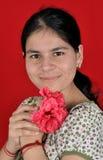 Muchacha de la espinilla con la flor Foto de archivo