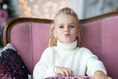 Muchacha de la Feliz Navidad y buenas fiestas de Litl que juega cerca del árbol de navidad foto de archivo