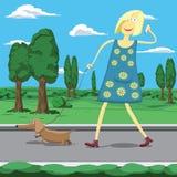 Muchacha de la historieta que camina un perro en el parque tolking en el teléfono móvil Imagen de archivo
