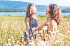 Muchacha de la madre y del niño en campo de la manzanilla Imágenes de archivo libres de regalías