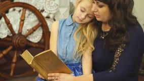 Muchacha de la madre y del niño que lee un libro en cama antes de ir a dormir almacen de video