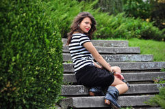 Muchacha de la manera que se sienta en las escaleras en parque Imagenes de archivo