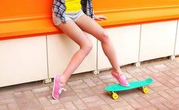 Muchacha de la moda con el monopatín sobre naranja colorida Fotos de archivo libres de regalías