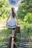 Muchacha de la moda con la maleta en los ferrocarriles Imagen de archivo libre de regalías
