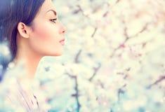 Muchacha de la moda de la primavera en árboles florecientes Imágenes de archivo libres de regalías