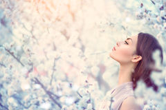 Muchacha de la moda de la primavera en árboles florecientes Fotografía de archivo libre de regalías