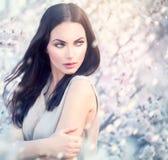Muchacha de la moda de la primavera en árboles florecientes Imagen de archivo libre de regalías