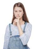 Muchacha de la moda de los jóvenes con el finger en los labios aislados Fotografía de archivo libre de regalías