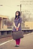 Muchacha de la moda de los jóvenes con la maleta en los ferrocarriles. Fotos de archivo