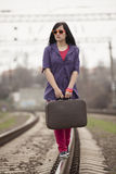 Muchacha de la moda de los jóvenes con la maleta en los ferrocarriles. Foto de archivo libre de regalías