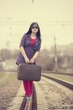Muchacha de la moda de los jóvenes con la maleta en los ferrocarriles. Imagen de archivo libre de regalías