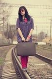 Muchacha de la moda de los jóvenes con la maleta en los ferrocarriles. Imagen de archivo