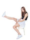 Muchacha de la moda de los jóvenes en la falda blanca que se sienta en la silla aislada Fotos de archivo