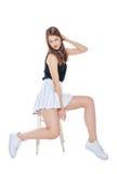Muchacha de la moda de los jóvenes en la falda blanca que se sienta en la silla aislada Imagen de archivo libre de regalías