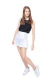 Muchacha de la moda de los jóvenes en la presentación blanca de la falda aislada Imagen de archivo