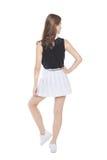 Muchacha de la moda de los jóvenes en la presentación blanca de la falda aislada back Foto de archivo
