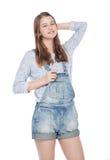 Muchacha de la moda de los jóvenes en la presentación de los guardapolvos de los vaqueros aislada Imagen de archivo libre de regalías
