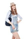 Muchacha de la moda de los jóvenes en la presentación de los guardapolvos y del sombrero de los vaqueros aislada Fotografía de archivo
