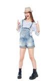 Muchacha de la moda de los jóvenes en los guardapolvos de los vaqueros con gesto del cuerno aislados Imagen de archivo