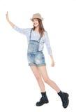 Muchacha de la moda de los jóvenes en los guardapolvos de los vaqueros que empujan algo aislada Imágenes de archivo libres de regalías