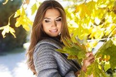 Muchacha de la moda de los jóvenes en parque del otoño Foto de archivo