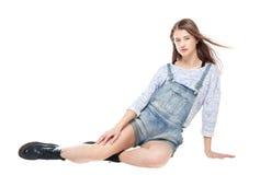 Muchacha de la moda de los jóvenes en sentarse de los guardapolvos de los vaqueros aislada Foto de archivo
