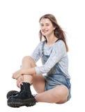 Muchacha de la moda de los jóvenes en sentarse de los guardapolvos de los vaqueros aislada Imagenes de archivo