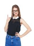 Muchacha de la moda de los jóvenes en vaqueros con gesto del cuerno aislada Imagen de archivo