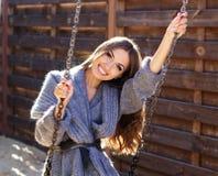 Muchacha de la moda de los jóvenes que se divierte en el oscilación Foto de archivo libre de regalías