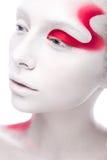 Muchacha de la moda del arte con la pintura blanca de la piel y del rojo encendido Fotos de archivo libres de regalías
