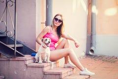 Muchacha de la moda del inconformista con su perro en la ciudad Imagenes de archivo