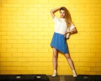 Muchacha de la moda del inconformista del estilo de la calle en la pared amarilla Imagenes de archivo