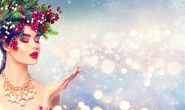 Muchacha de la moda del invierno de la Navidad con nieve mágica en su mano imagen de archivo libre de regalías