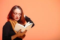 Muchacha de la moda del otoño con las pestañas de la naranja del libro imagenes de archivo