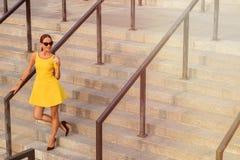 Muchacha de la moda que presenta con el cóctel anaranjado Imágenes de archivo libres de regalías