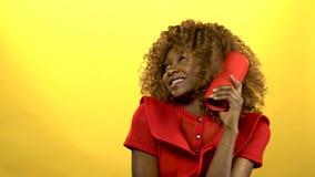Muchacha de la mujer afroamericana que celebra un artilugio y un baile del jugador Fondo amarillo almacen de video
