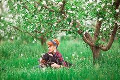 Muchacha de la mujer con el perro Berna en jardín de la primavera, Imagen de archivo