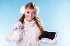Muchacha de la mujer con la tableta y el pequeño muñeco de nieve Invierno Imágenes de archivo libres de regalías